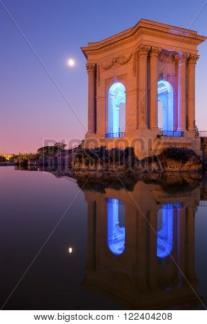 Chateau d'Eau palace - water tower in the end of aqueduct in Montpellier, France. Illuminated at night.