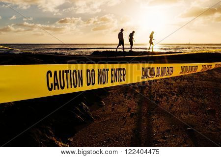 Caution Do Not Enter yellow tape on a beach at sunset and silhouette of three people behind it