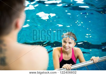 Female swimmer in an indoor swimming pool - talking to a friend (shallow DOF)