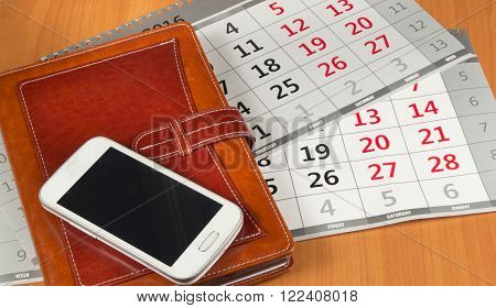 Brown personal organizer or planner with a mobile phone and a calendar on the desktop.