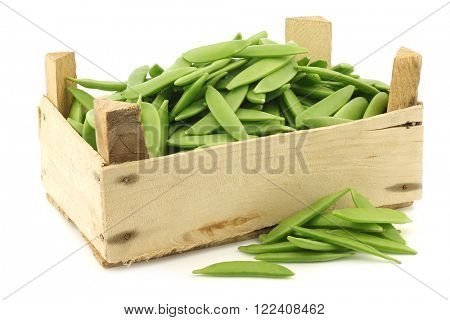 sugar snaps in a wooden crate on a white background