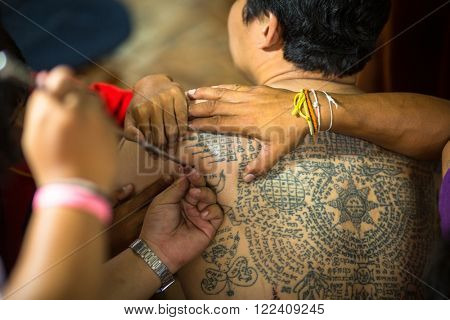 WAT BANG PHRA, THAILAND - MART 18, 2016: Unidentified monk makes traditional Yantra tattooing during Wai Kroo Master Day Ceremony in Bang Pra monastery, about 50 km west of Bangkok.