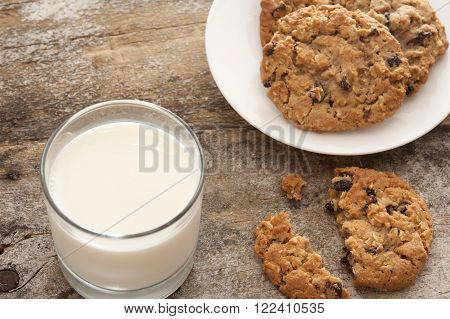 Milk and cookies in childhood tradition with a glass of farm fresh creamy milk and plate of choc chip cookies with one broken one on the old rustic wooden table
