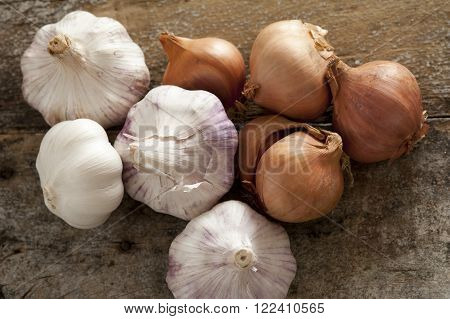 Fresh raw whole garlic bulbs and brown onions both of the Allium family on a rustic wooden table viewed from overhead
