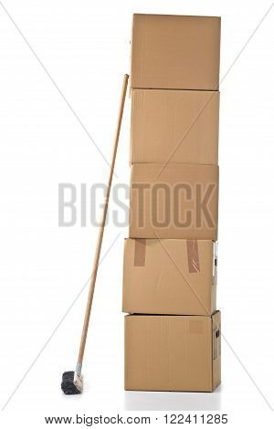 Stacked moving carton boxes with broom over white background