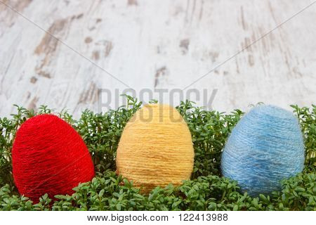 Easter eggs wrapped woolen string and green cuckooflower cress on old wooden background copy space for inscription or text decoration for Easter