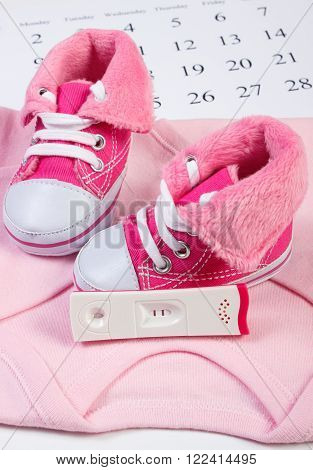 Pregnancy test with positive result and clothing for newborn on calendar baby shoes bodysuits concept of extending family and expecting for baby