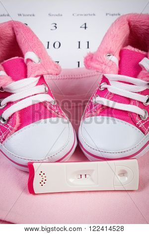 Pregnancy test with positive result and clothing for newborn on calendar, baby shoes, bodysuits, concept of extending family and expecting for baby
