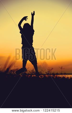 Silhouette Of Child Jumping Against Sunset. Boy Enjoying The View.