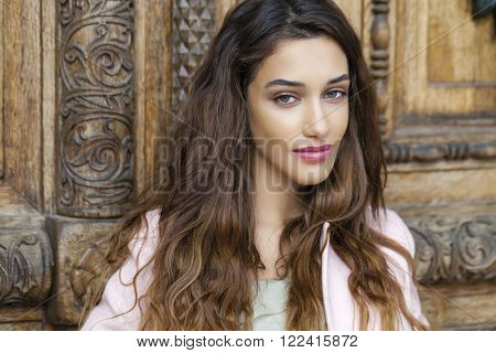 Sexy young brunette woman in dress, against the background of an old wooden door