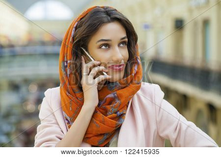 Close up portrait of a muslim young woman wearing a head scarf calling by phone