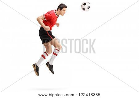 Full length profile shot of a male football player heading a ball shot in mid-air isolated on white background