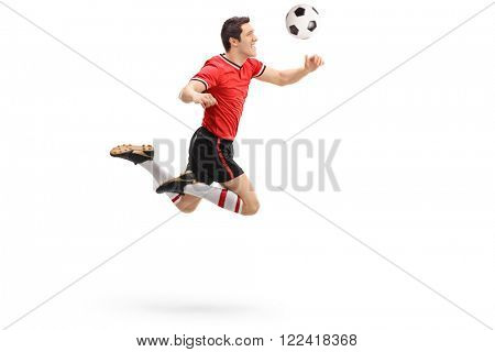 Studio shot of a young football player heading a ball shot in mid-air isolated on white background