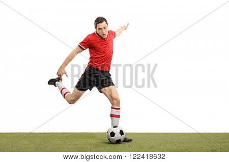Young football player kicking a ball and playing football on a grass field isolated on white background