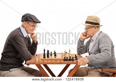 Two senior gentlemen playing chess and contemplating their next move isolated on white background