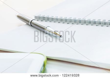 Open notebook with metallic ball pen and tablet. Selective focus.