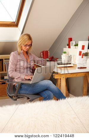 Blonde woman browsing internet on laptop computer at home, sitting in study.