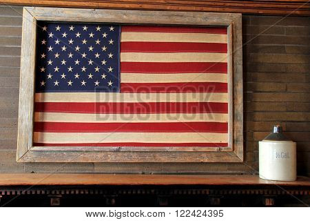 Rustic image of American flag framed in wood, hanging over mantle of fireplace