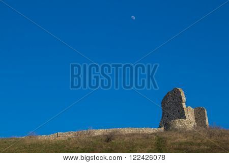Part of the former fortress ruins of the Devin castle Bratislava Slovakia. Surrounding wall and a building on the hill. Bright blue sky with a moon.
