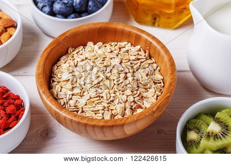 Healthy breakfast - bowl of oat flakes with fresh fruit almond and honey selective focus.