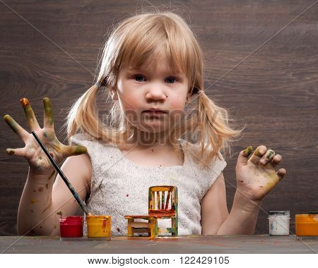 Funny little girl. Hands in the paint. Funny Face. On the table and paint a toy chair. Girl draw, paint paint a chair