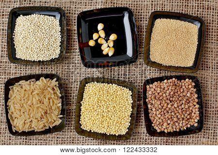 Rice, Quinoa, Corn, Millet, Buckwheat, Amaranth In Black Plate On The Gunny Cloth