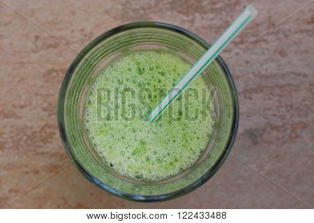 Green smoothie from spinach with the straw