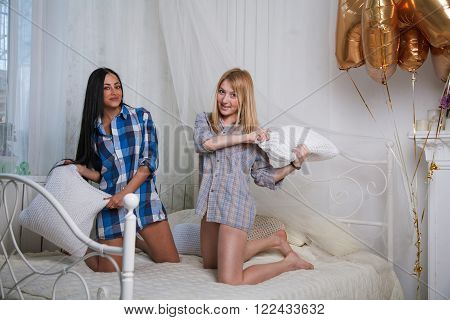 Beautiful sexy two girls having fun in bedroom pillow fight. Blonde woman and brunette lady smiling looking at camera.