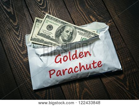 Golden parachute. American Dollars in the Envelope on the Table