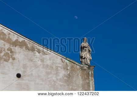 Diagonal line of the roof of the Church of Saint Cross in Devin Bratislava Slovakia. Statue of a saint. Bright blue sky with a moon.