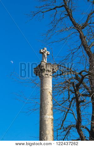 Column with a cross under old big tree. Bright blue sky with a moon. Devin Bratislava Slovakia.