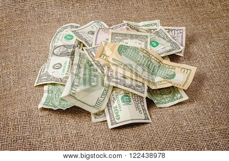 Pile of US dollar banknotes crumpled on rustic jute background