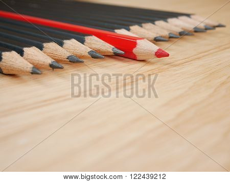Red pencil standout from black pencil on wood background leadership business concept