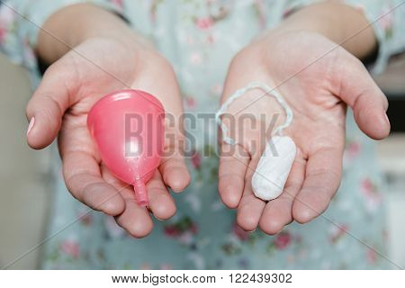 Close up of woman hands holding tampon and menstrual cup. Comparation of different methods of female intimate hygiene.
