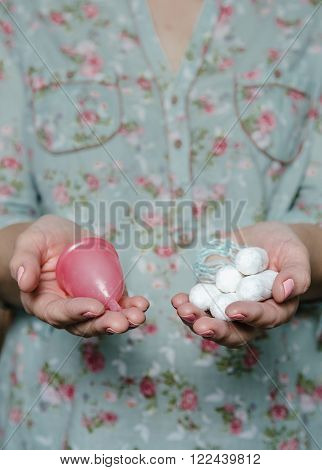 Woman hands holding tampons and menstrual cup. Comparation of different methods of female intimate hygiene.