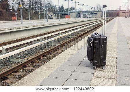 black suitcase left alone on platform at trainstation