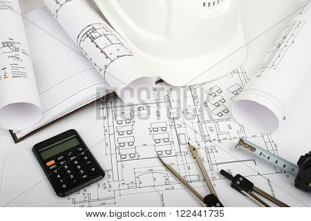 Architecture plan and rolls of blueprints with hard hat and calculator. Building concept