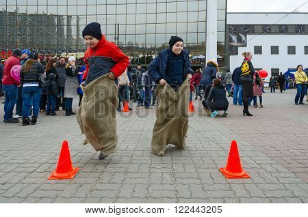 GOMEL BELARUS - MARCH 12 2016: Unidentified children participate in cheerful jesting competition Jumping in bags during Shrovetide festivities