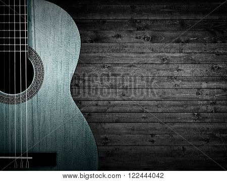 Part of a blue acoustic guitar on a gray wooden background