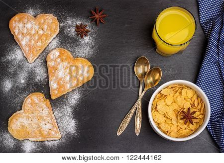 Still life, food and drink concept. Breakfast with belgian waffles and corn flakes on a grunge stone table. Selective focus, top view