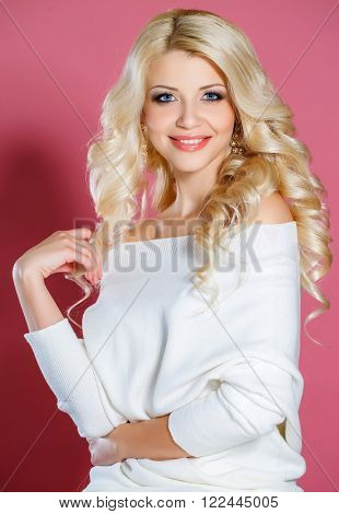 Studio portrait of a beautiful woman,with long blonde curly hair,blue eyes,pink lipstick,light makeup,gold earrings in her ears,dressed in a short white dress,poses for photographer in Studio on pink background