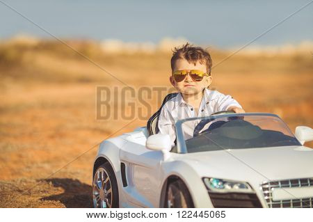 The young driver,a boy with brunette short hair,mirrored sun glasses yellow,in white shirt posing on a mountain road against the sea and clear sky,sitting in a posh toy car white color in the fresh summer air