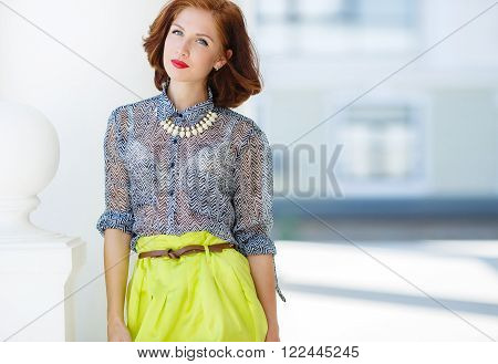 Fashion woman with brown hair and stylish hair,gray eyes and red lipstick,dressed in lemon-colored skirt and gray blouse,wears a white necklace,red nail Polish,posing on the street in the city in the summer