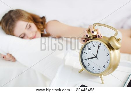 Young beautiful redhead woman with long curly hair ,dressed in a white nightshirt asleep on a soft pillow in a white bed in bright bedroom on a large white bed ,a big alarm clock Golden color shows 8.00