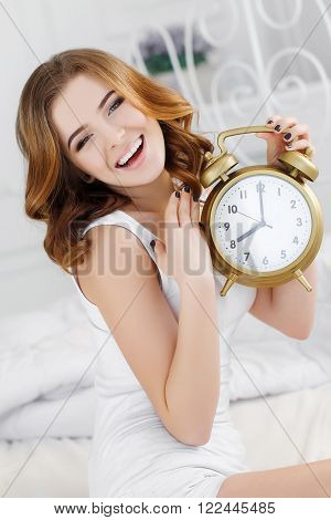 Young beautiful redhead woman with long curly hair ,dressed in a white nightgown wakes up in the morning on a soft pillow in a white bed in bright bedroom in a beautiful vintage white bed at 8.00 on a call of a large alarm clock