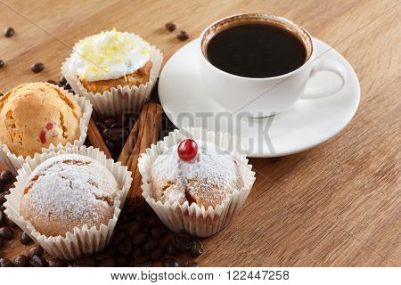 Sweet muffin and coffee on wooden background tasty breakfast. Coffee beans. Closeup.