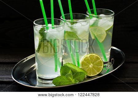Mojito cocktail with rum lime mint and soda in a highball glass on a metal tray