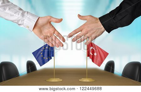 European Union and Turkey diplomats shaking hands to agree deal