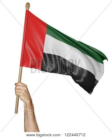 Hand proudly waving the national flag of the United Arab Emirates