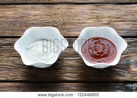 Food - ketchup and mayonnaise sauce. Two sauces on wood. Dip and dressing at wooden table. Pair of sauces closeup.  Tomato and sour cream sauces in white bowls.